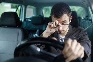 Drowsy Driver tired holding the wheel of his car